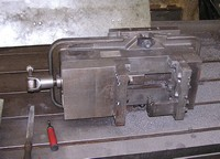 Conventional vise with custom vise jaws to hold cast iron part.  Machined on a CNC vertical machining center