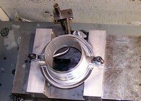 Conventional vise holding an aluminum part that was CNC turned. Aluminum 	vise jaws were machined to hold the round part.